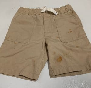 Khaki shorts on white background with pizza sauce stains